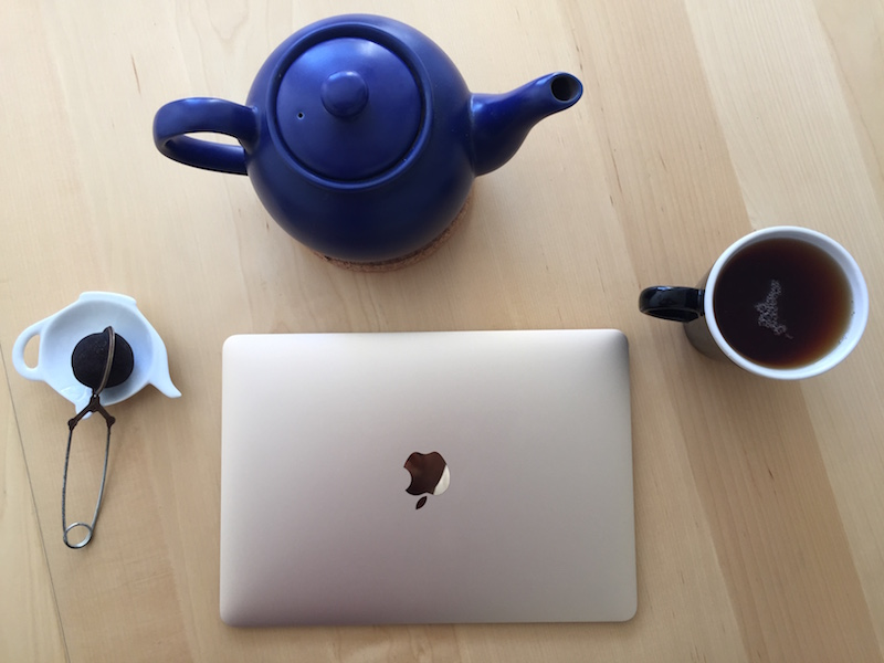 2015 Macbook on table, with common tea utensils for reference