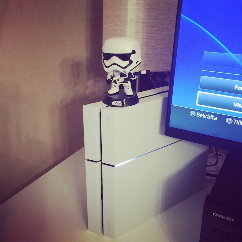 White Playstation 4, with Star wars stormtrooper figure on top